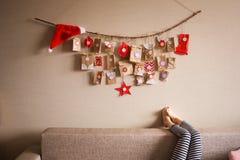 Le calendrier d'avènement accrochant sur le mur petites surprises de cadeaux pour des enfants photographie stock libre de droits