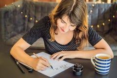 Le calligraphe Young Woman ?crit l'expression sur le livre blanc Inscrire les lettres d?cor?es ornementales Calligraphie, graphiq images stock