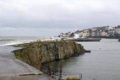 Le calme arrose à l'intérieur du long port abrité de trou dans le comté de Bangor vers le bas tandis qu'une tempête fait rage en  Photo stock