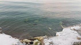 Le calme ondule sur l'eau de fjord frappant le bord de mer neigeux en Norvège du nord banque de vidéos