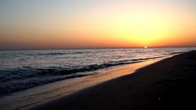 Le calme satisfaisant lent ondule se briser sur le littoral de bord de mer de plage de sable dans le paysage marin orange de couc banque de vidéos