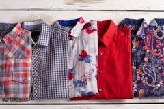 Le camice variopinte degli uomini con differenti stampe Immagine Stock