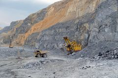 Le camion à benne basculante Caterpillar a chargé avec des tractions de minerai de néphéline à partir de l'excavatrice image libre de droits