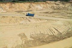 Le camion à benne basculante se déplace sur un fond de bac à sable Photographie stock libre de droits