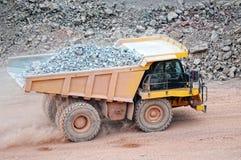 Le camion de déchargeur conduisant dans une mine active de carrière de porphyre bascule photographie stock libre de droits