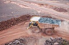 Le camion de déchargeur conduisant dans une mine active de carrière de porphyre bascule images libres de droits