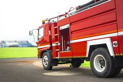 Le camion de pompe à incendie se tiennent prêt près de la piste de roulement d'aéroport avec l'avion de tache floue à l'arrière-p Photographie stock