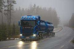 Le camion de réservoir bleu de Scania R580 pousse en avant en brouillard Images libres de droits
