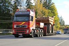 Le camion de Volvo transporte des machines de construction en tant que charge large Photos stock