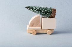 Le camion en bois de jouet avec l'arbre de Noël est allumé supérieur image stock