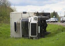 Le camion fourgon-réfrigéré inversé de cargaison se situe dans un fossé photo stock