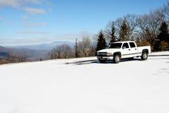 Le camion pick-up blanc se reposant sur une neige a couvert la montagne de beau ciel et de vue d'autres montagnes dans la distanc Photo stock