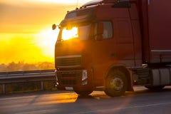 Le camion va sur la route sur le coucher du soleil Image libre de droits