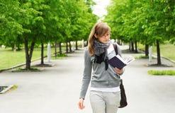 Le camminate della ragazza, leggenti il libro Immagini Stock Libere da Diritti