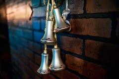 Le campane di Natale appendono come decorazione sul nastro sul muro di mattoni Fotografia Stock