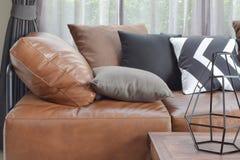 Le canapé-lit en cuir brun clair avec varie des oreillers de couleur et de taille Image libre de droits