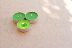 Le candele aromatiche verdi sul bordo di legno con possiedono la luce Fotografie Stock