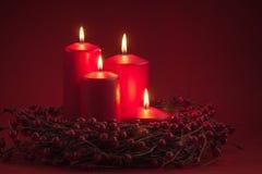 Le candele brucianti rosse di Advent Christmas con le bacche si avvolgono su un fondo rosso Fotografia Stock