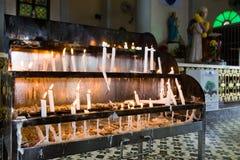 Le candele dispongono con le candele brucianti all'interno della chiesa cattolica Fotografie Stock Libere da Diritti