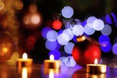 Le candele dorate di Natale e le bagattelle rosse con l'albero brillante si accende Fotografia Stock