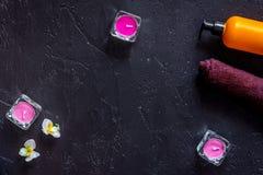 Le candele e la lozione per l'aroma si rilassano il bagno sul copyspace nero di vista superiore del fondo della tavola Fotografia Stock