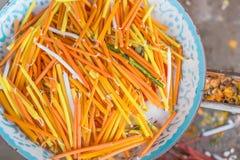Le candele gialle, bianche ed arancio sono nel vassoio del metallo sfuocato Fotografia Stock Libera da Diritti