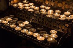 Le candele hanno acceso i parrocchiani nella chiesa cattolica Immagine Stock