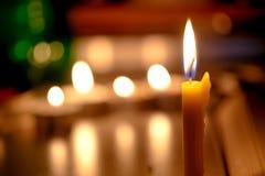 Le candele si accendono con il fondo vago del libro nella chiesa Fotografie Stock