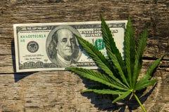 Le cannabis verdi coprono di foglie e banconota in dollari 100 sulla tavola di legno Fotografia Stock