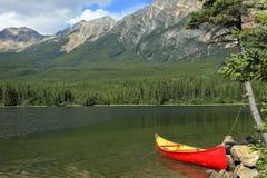 Le canoë rouge a amarré sur le côté Photographie stock libre de droits