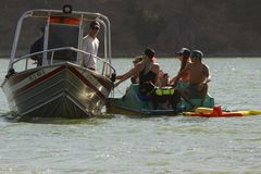 Le canot automobile américain de délivrance remorque un catamaran avec des passagers Photos libres de droits