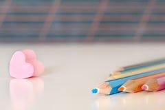 Le caoutchouc et crayons de coeur contre un tableau noir rayé Image stock