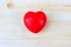 Le caoutchouc rouge de coeur sur la table en bois Photographie stock