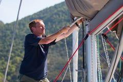 Le capitaine serre les cordes sur son yacht de navigation sport Images libres de droits