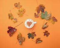Le cappuccino avec l'érable de forme et d'automne de coeur part autour de lui Photographie stock