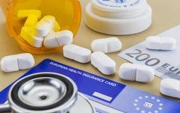 Le capsule aumentano l'euro del biglietto e la carta europea dell'assicurazione malattia fotografia stock libera da diritti