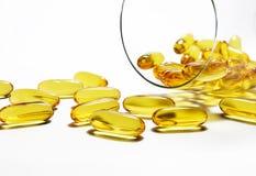 Le capsule dell'olio di pesce versano sul pavimento bianco Fotografia Stock Libera da Diritti