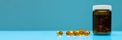 Le capsule della bottiglia e del medicinale del farmaco su pastello blu hanno colorato il fondo Farmaco ed insegna di web delle p Fotografie Stock