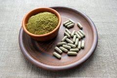 Le capsule e la polvere verdi su un'argilla bruniscono il piatto su una ruggine della tela da imballaggio immagini stock
