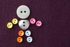 Le caractère drôle fait en couture colorée se boutonne avec le bouton de central de forme de coeur d'amour fond texturisé violet  Photos stock