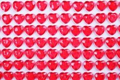 Le caramelle del cuore di rossi carmini hanno risieduto in una fila su fondo bianco Regalo della cartolina d'auguri di giorno deg Fotografia Stock