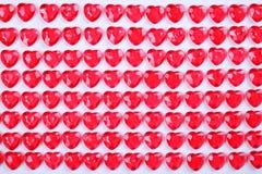 Le caramelle del cuore di rossi carmini hanno risieduto in una fila su fondo bianco Regalo della cartolina d'auguri di giorno deg Fotografia Stock Libera da Diritti