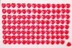 Le caramelle del cuore di rossi carmini hanno risieduto in una fila su fondo bianco Regalo della cartolina d'auguri di giorno deg Immagine Stock