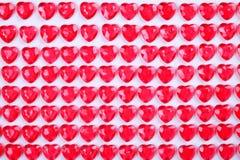 Le caramelle del cuore di rossi carmini hanno risieduto in una fila su fondo bianco Regalo della cartolina d'auguri di giorno deg Fotografie Stock