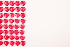 Le caramelle del cuore di rossi carmini hanno risieduto in una fila su fondo bianco Regalo della cartolina d'auguri di giorno deg Fotografie Stock Libere da Diritti