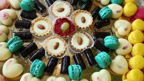 Le caramelle di cioccolato, dolci con le mandorle, le pasticcerie in forma di cuore, paste sono messe su una tavola di buffet video d archivio