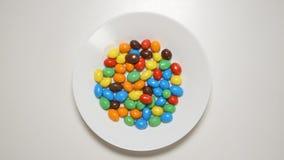 Le caramelle variopinte compaiono su un piatto bianco su una tavola bianca fermano il moto stock footage
