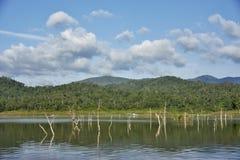 Le carcasse di legno sull'acqua e sul cielo blu riflette la superficie in diga di Srinakarin, provincia di Kanjanaburi Fotografie Stock Libere da Diritti