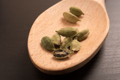 Le cardamon sec frais de cardamome sème l'épice sur une cuillère en bois Photos libres de droits