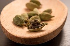 Le cardamon sec frais de cardamome sème l'épice sur une cuillère en bois Photo stock